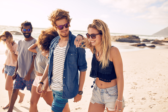 Diverse group of young friends having a walk on the beach - Signs A Scorpio Man Likes You